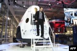 Илон Маск на фоне перспективного пилотируемого семиместного корабля Dragon V2