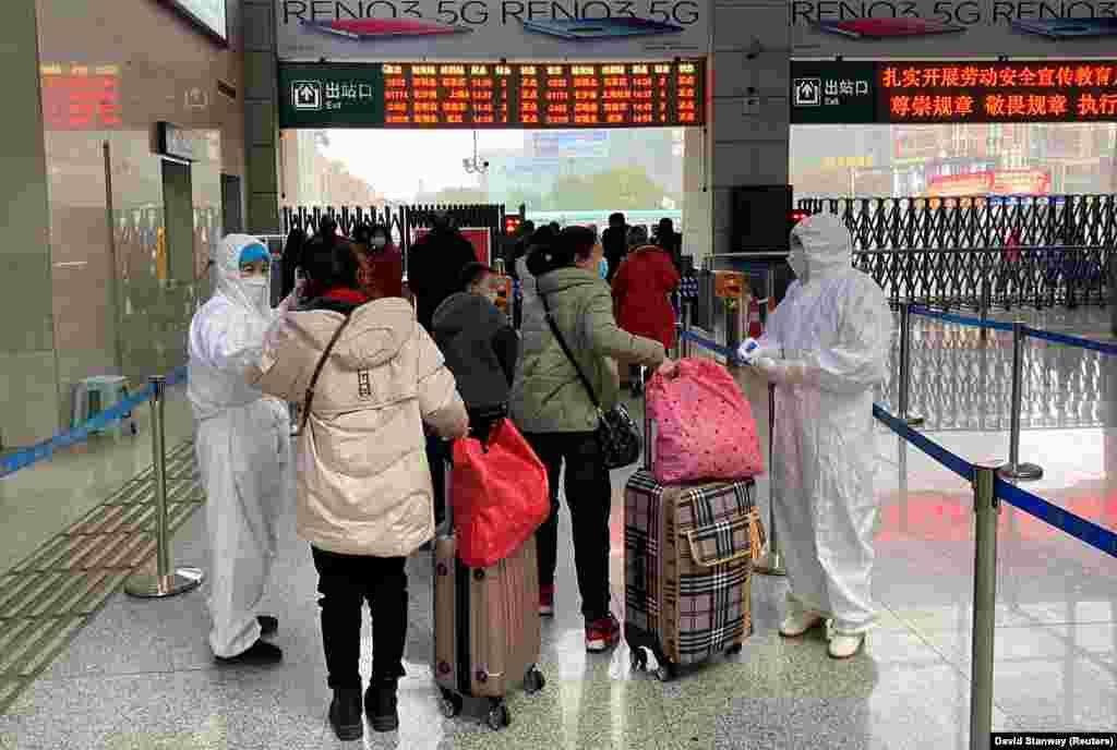 Медицинские сотрудники проверяют температуру у пассажиров, прибывших на Северный железнодорожный вокзал соседнего с Уханем города Сяньнин. 24 января 2020 года.