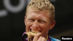 Kazahstanac Aleksandr Vinokurov grize zlatnu medalju za osvojeno porvo mjesto u biciklizmu na hronometar, 28, juli 2012.