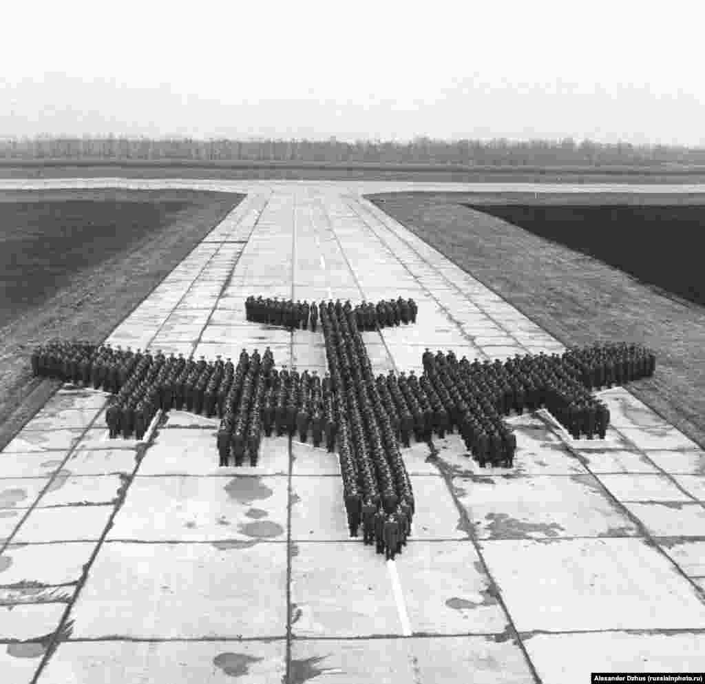 Plane-shaped crowd, on a runway in 1980.