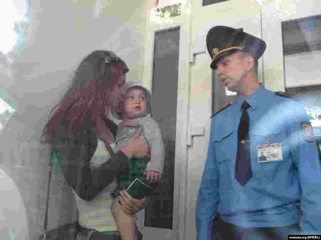 Жонку журналіста Аксану Пачобут з дзіцём на руках ў тамбуре суду не пускае ўнутр міліцыянт