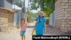 Azerbaijan -- Residents walk a village in Aghdam district located near the contact line with the Armenian troops – Aug2014