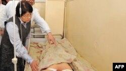 Убактылуу өкмөт жетекчиси Роза Отунбаева каршылык акциясында жарадар болгон жарандын абалын сурап жатат.