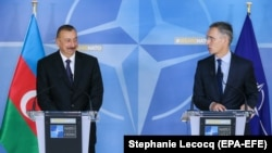 Azerbaijani President Ilham Aliyev (left) and NATO Secretary-General Jens Stoltenberg give a press conference at the end of a meeting at NATO headquarters in Brussels on November 23.
