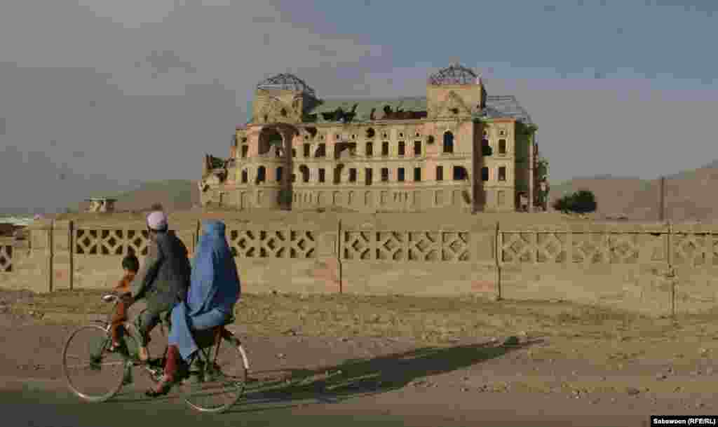 A family rides past the destroyed Darull Aman Palace.