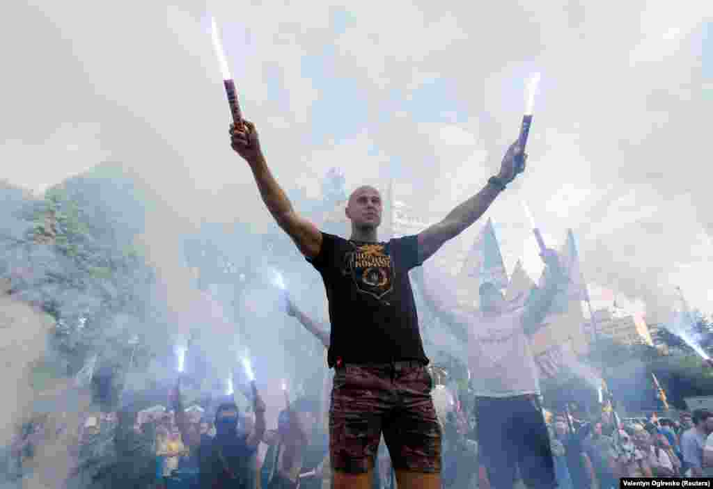 Protesters burn flares as they demand that several Ukrainian lawmakers, suspected of corruption by the prosecutor-general's office, be deprived of parliamentary immunity during a rally near the parliament building in Kyiv on July 11. (Reuters/Valentyn Ogrienko)