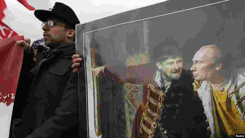 Participants hold a painting depicting Russian President Vladimir Putin (right) and pro-Kremlin Chechen leader Ramzan Kadyrov.