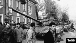 Сүрөттө: Тажикстандагы 1990-жылдардагы атуулдук согуштун бир учуру. Өзбек колбашчы, полковник Махмуд Худайбердиев жетектеген өкмөттүк жоокерлер Түндүк Тажикстандагы Турсунзаде шаарында көтөрүлүшчү Надыр Абдуллаевдин күчтөрүн шаар сыртына сүрдү.