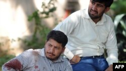 A blood-covered UN employee sits outside his office after a suicide blast in Islamabad on October 5.