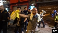 A pro-democracy protester wearing goggles to protect his eyes from chemical agents gestures as police advance toward him and other demonstrators during clashes on a street in the Mongkok district of Hong Kong early on October 19.