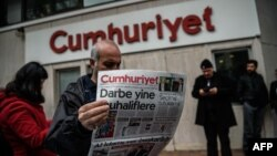 Turkey -- A man reads a copy of Cumhuriyet daily newspaper in front of the newspaper's headquarters in Istanbul during a police operation, October 31, 2016
