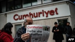 A man reads a copy of the Cumhuriyet daily newspaper in front of the newspaper's headquarters in Istanbul during a police operation on October 31.