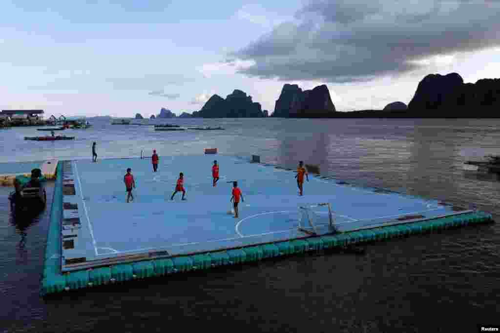 Дети играют на футбольном поле, сооруженном на поверхности воды. Таиланд, 20 мая 2018 года.