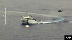Спасательное судно и вертолет во время поисково-спасательных операций в Средиземном море. 19 апреля 2015 года.