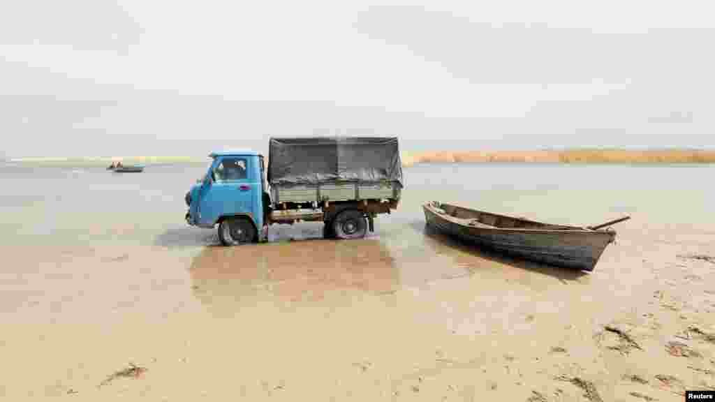 Рыбаки приезжают на грузовике, чтобы собрать рыбу с лодки на мелководье у Аральского моря.