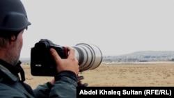 Журналист выполняет свою работу недалеко от сирийского города Кобани.