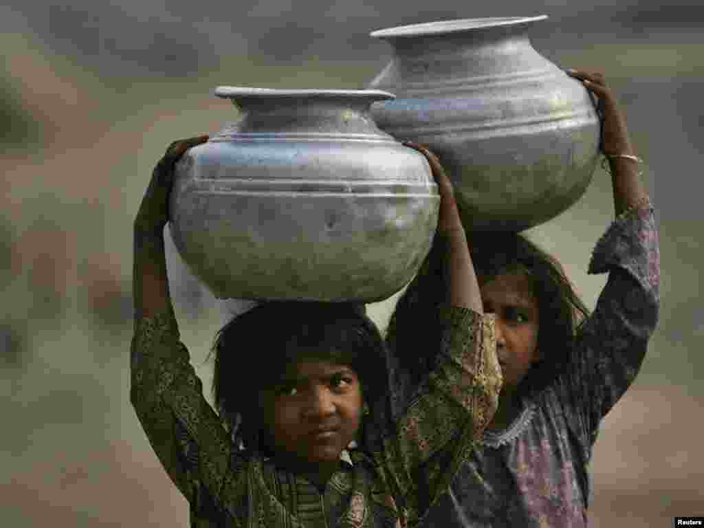 Pakistani girls carry water from a well on the outskirts of Lahore. - Photo by Mohsin Raza for Reuters