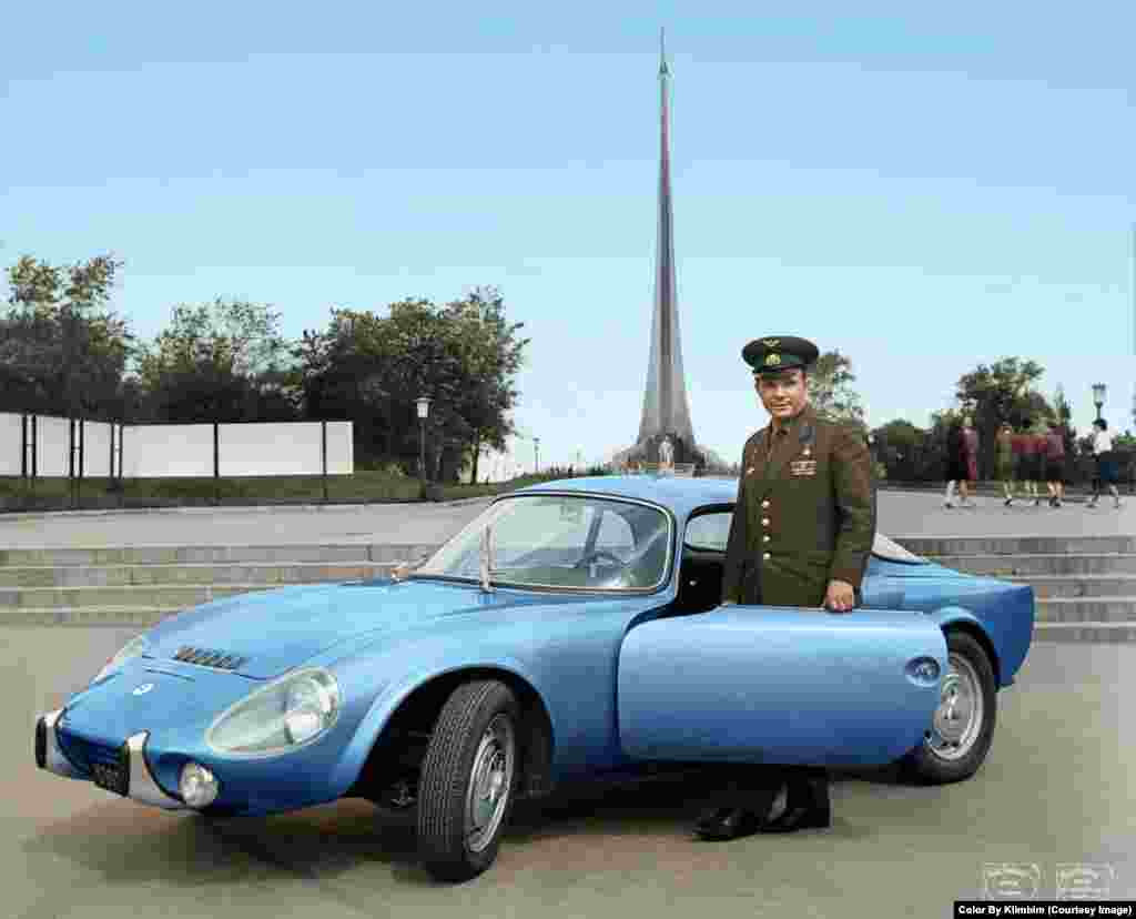 Yury Gagarin in front of a monument to space exploration in Moscow. The Soviet cosmonaut is posing with his Matra Djet sports car, a gift from the French government.