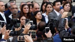 Луѓе снимаат со мобилни телефони додека говорат членови на Демократската партија на народите (ДПН).