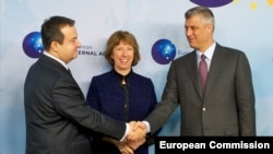 Serbia's Ivica Dacic (left) and Kosovo's Hashim Thaci shake hands in Brussels in December 2013 as EU foreign-policy chief Catherine Ashton looks on.