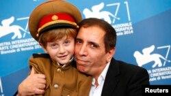 Ирандық режиссер Мохсен Махмальбаф (оң жақта) «Президент» фильміне түскен Дачи Орвелашвилиді құшақтап отыр. Венеция, 27 тамыз 2014 жыл.