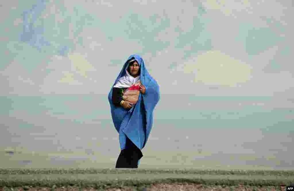 An Afghan woman holding her child waits for transportation on the outskirts of Herat. (AFP/Aref Karimi)