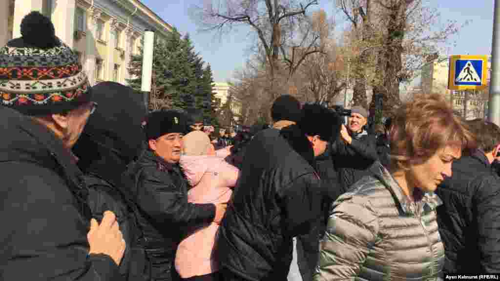 Полиция кейбір азаматтарды көлікке күшпен жеткізді.