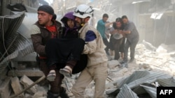 Syria -- Syrian civil defence volunteers evacuate wounded people following a reported airstrike in the rebel-held neighbourhood of Hayy Aqyul in the city of Aleppo, April 22, 2016