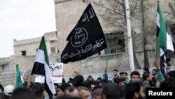 """Идлиб провинциясындағы үкіметке қарсы шеруде демонстранттар """"Әл-Қаида"""" туын (ортада) ұстап жүр. Сирия, наурыз 2016 жыл (Көрнекі сурет)."""
