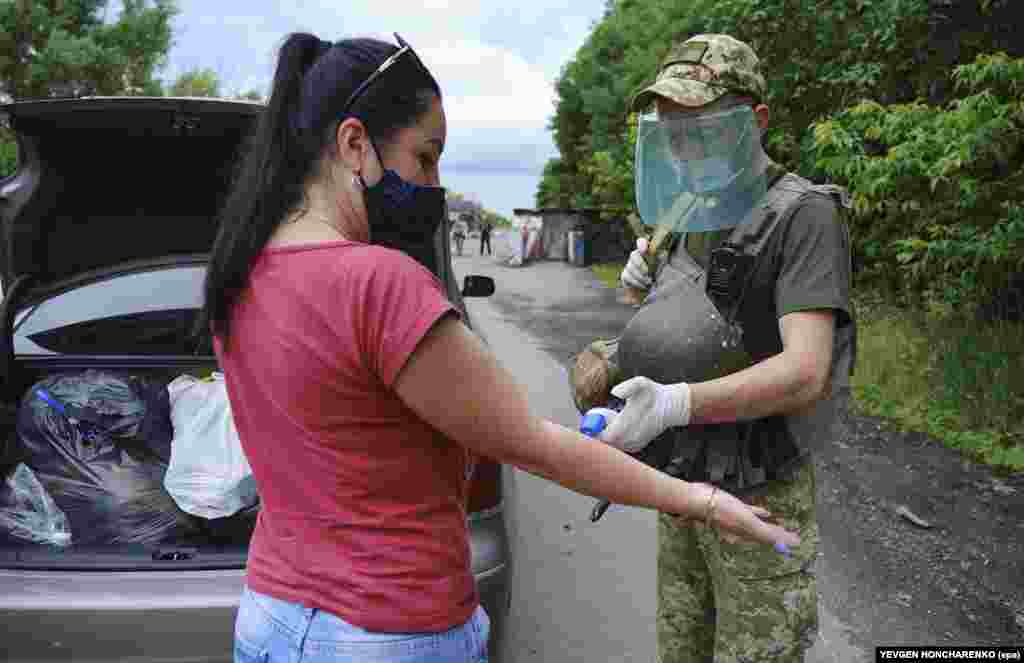 A Ukrainian soldier checks the temperature of a woman at a checkpoint between Ukrainian and separatist-controlled territories near Donetsk shortly after the crossing point was reopened. The photo was taken on June 22.