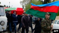 Men carry the coffin of an Azerbaijan's serviceman, who was killed on April 2 during clashes between Armenian and Azeri forces in Nagorny Karabakh, during his funeral in Terter on April 3, 2016.