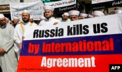 Members of the Sunni Committee of Muslim Scholars hold a banner protesting Moscow's intervention in Syria outside the Russian embassy in Beirut, Lebanon, on October 14.