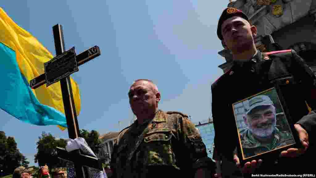 У руках військового фотографія загиблого Сергія Баули (позивний «Ворон»)