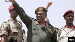 Президент Судана Омар аль-Башир приветствует участников митинга против повстанцев. Хартум, 14 мая 2008 года.