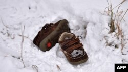 A pair of shoes belonging to a child lie in a snow-covered field in the northern Serbian village of Backi Vinogradi near the Hungarian border.