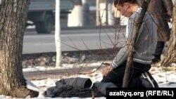 Фурманов көшесі бойында намаз оқып отырған жігіт. Алматы, 28 қараша 2012 жыл. (Көрнекі сурет)