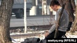 Фурманов көшесінің бойында намаз оқып отырған жігіт. Алматы, 28 қараша 2012 жыл. (Көрнекі сурет)
