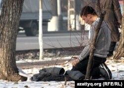 Көше бойында намаз оқып отырған жігіт. Алматы, 28 қараша 2012 жыл.