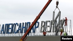 "Workers dismantle the ""Alexander the Great"" sign at Macedonia's Skopje airport on February 24."