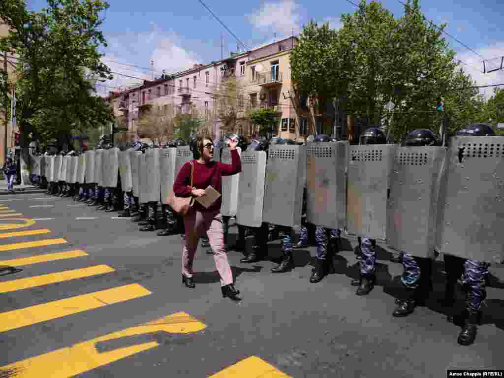 "An Armenian woman confronts a line of riot police blocking Yerevan's Mashtots avenue: ""I'm a journalist but before I'm a journalist I'm a citizen, and before you are police you are all citizens of Armenia!"" (RFE/RL /Amos Chapple)"