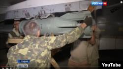 """Российские военные прикрепляют бомбу ОФАБ-250 к штурмовику Су-25, кадр из сюжета телеканала """"Россия 24"""""""