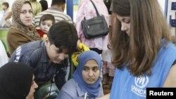 عاملة اغاثة دولية مع نازحين عراقيين الى سوريا