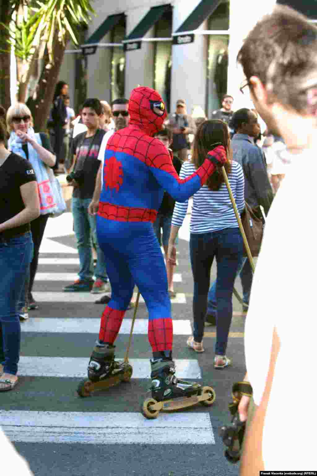 A man in a Spiderman costume skates through the streets of Cannes.