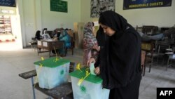 Pakistan -- A woman casts her vote at a polling station during the country's by-election in several constituencies, in Islamabad, August 22, 2013