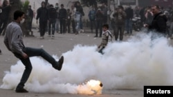 An Egyptian protester kicks a gas canister during clashes with security forces in Cairo.
