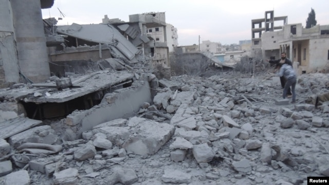 Residents stand near buildings damaged by what activists said were missiles fired by a Syrian Air Force fighter jet loyal to President Bashar al-Assad in Binsh near Idlib on January 2.