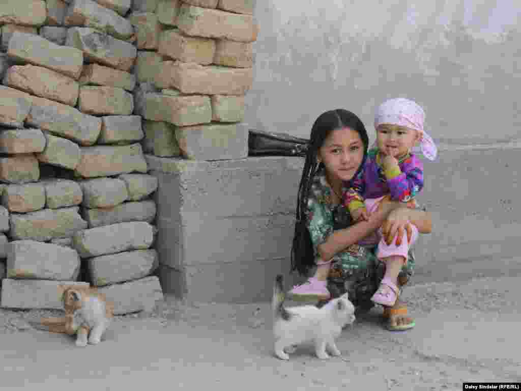 Ten-year-old Madina, an ethnic Uzbek, holds her niece in the courtyard of her family home in an Uzbek mahalla in the southern Kyrgyz city of Osh. Her family's home was destroyed by fire in the June 2010 ethnic clashes. A report by the international Kyrgyzstan Inquiry Commission says Uzbeks made up three-fourths of the 470 people killed in the clashes and also sustained the majority of the property damage.