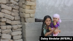Ten-year-old Madina, an ethnic Uzbek, holds her niece in the courtyard of her family home in an Uzbek mahalla in the southern Kyrgyz city of Osh. Her family's home was destroyed by fire in the June 2010 ethnic clashes.