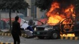 A lawyer throws a trash can toward police near a vehicle set on fire outside the Punjab Institute of Cardiology (PIC) in Lahore on December 11.
