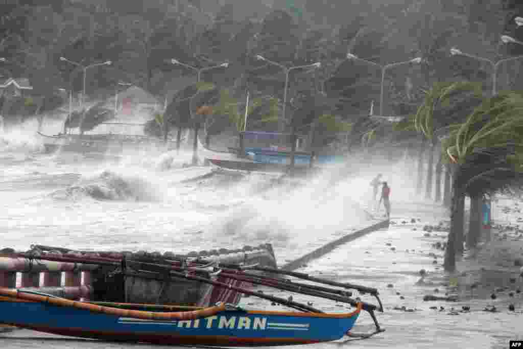 Philippines -- A resident (R) walks past high waves pounding the sea wall amidst strong winds as Typhoon Haiyan hit the city of Legaspi, Albay province, south of Manila on November 8, 2013.